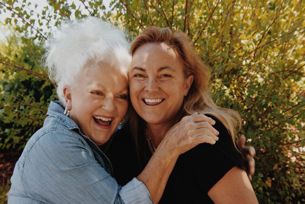 younger and older woman hunging and smiling